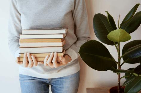 Bücherstapel in den Händen